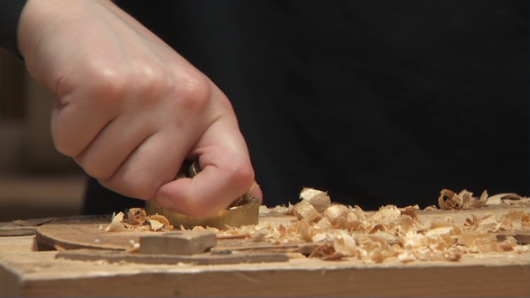 13-year-old Ben Milne uses a wood plane to scrape away filings, part of the process for making a violin.
