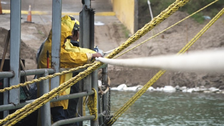 Ferry operators pull on a cable to move El Chalan back and forth between the US and Mexico