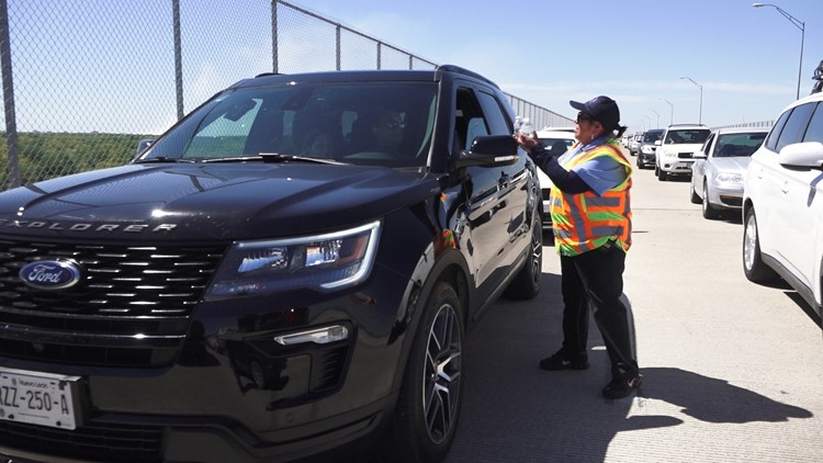 Dora Zamora hands out bottles of water to travelers waiting to cross the US-Mexico border at the Anzalduas International Bridge