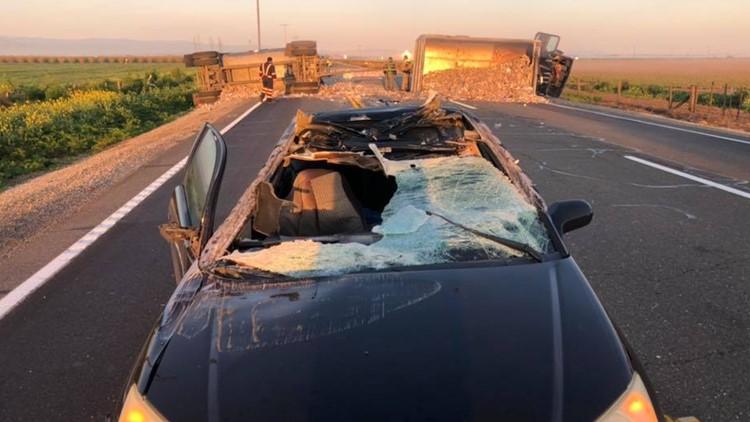 Car limbos under overturned trailer
