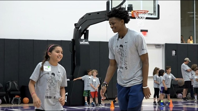 Sacramento Kings guard De'Aaron Fox interacts with a participant of Saturday's charity basketball clinic at the team's practice facility inside the Golden 1 Center. (PHOTO: Sean Cunningham/KXTV)