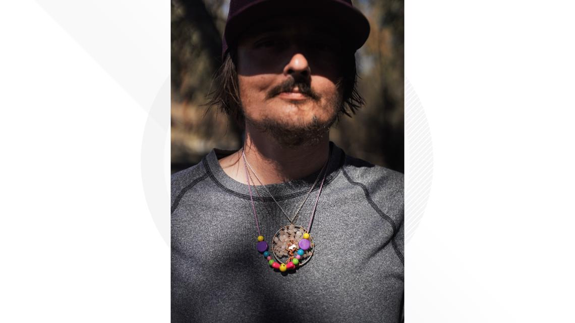 Zach McLeod stands for a portrait, wearing a pair of necklaces made by his wife Alaina McLeod and their daughter Feyla, who were both killed in the Zogg Fire.
